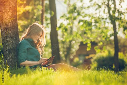 Fototapeta Pretty young caucasian woman  sitting outside under a tree obraz