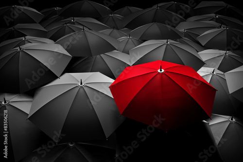 Red umbrella stand out from the crowd. Different, leader.