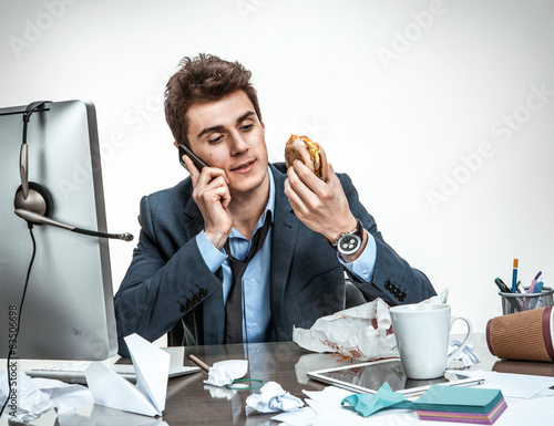 Photo Slacker man talking on the phone while eating at work