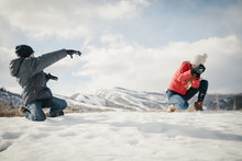 A Snowball Fight Between A Brother And Sister.