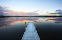 View Over A Calm Lake, And A Dock Out Over The Water.