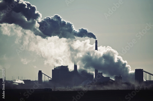 Heat, steam and smoke rising from chimneys of power plant