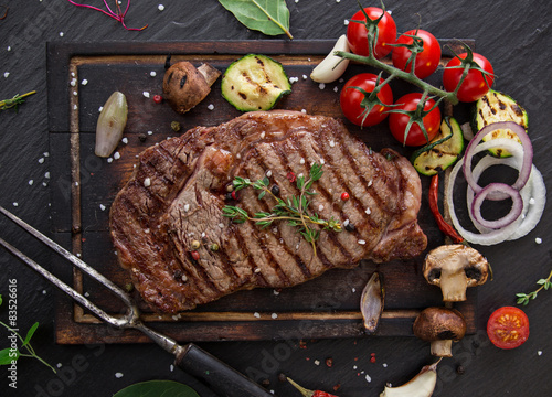Fotografering  Beef steak on wooden table
