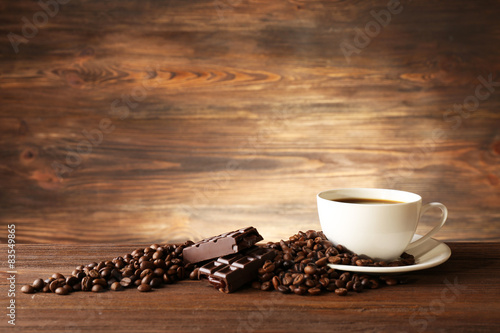 Tuinposter koffiebar Cup of coffee with grains on wooden background