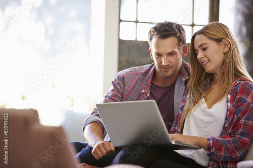 Plakat Para w domu w salonie przy użyciu komputera przenośnego