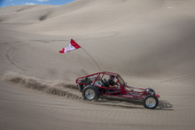Red Sand Dune Buggy Racing By In The Sand Dunes