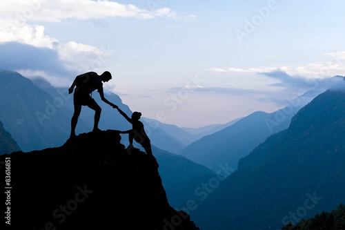 Fotografie, Obraz  Teamwork couple climbing helping hand