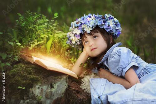 Fotografie, Obraz  Reading fairy tales by a little girl in a meadow