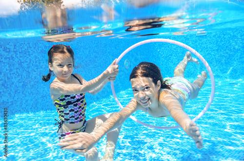 Happy children swim in pool underwater, girls swimming Slika na platnu
