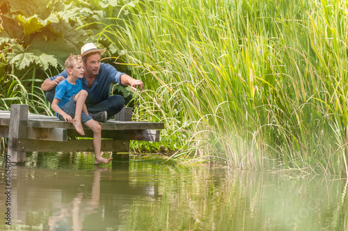 Fotografia On a wood pontoon, father teaching his young son to respect nature