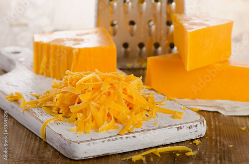 Grated Cheddar Cheese on a Cutting Board.