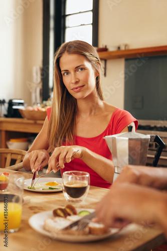 Foto op Canvas Kruidenierswinkel Young woman having breakfast in kitchen at home