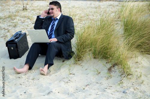 Fotografie, Obraz  Geschäftsmann sitzt am Sandstrand und arbeitet am Computer