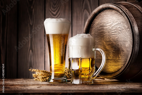 Photo  Mug and a glass of light beer with ears of barley