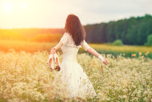 Young Bride Holding Shoes Walking On The Flower Meadow