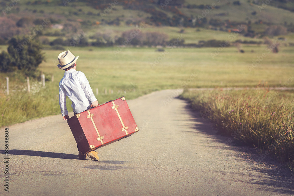 Fototapeta niño con maleta en la carretera