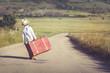 Leinwandbild Motiv niño con maleta en la carretera