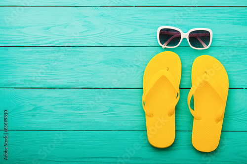 Flip flops and sunglasses on blue wooden background