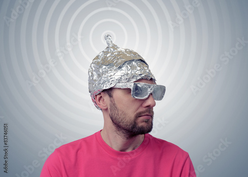 Fotografie, Obraz  Bearded funny man in a cap of aluminum foil sends signals