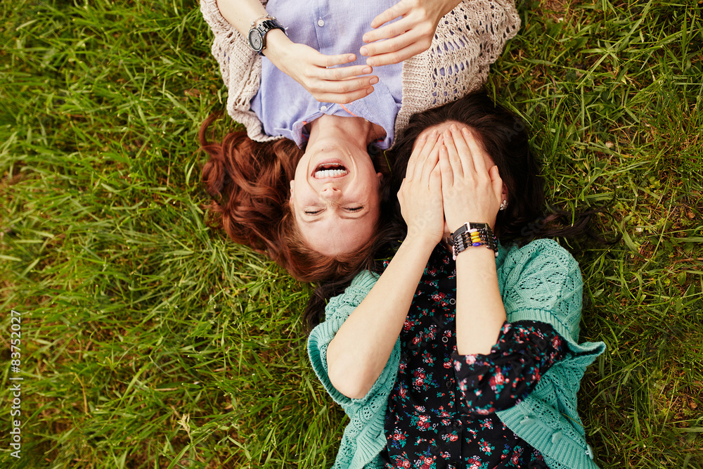 Fototapety, obrazy: Two cheerful sisters lying on the grass