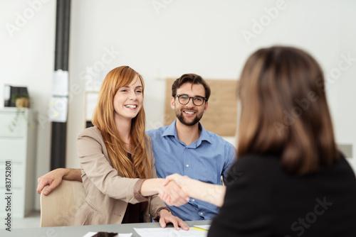 Fototapeta glückliches paar schüttelt beraterin die hand obraz