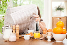 Woman Is Reading A Newspaper While Having Breakfast