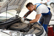 Closeup Portrait of Mechanic Servicing a Car at His Workshop