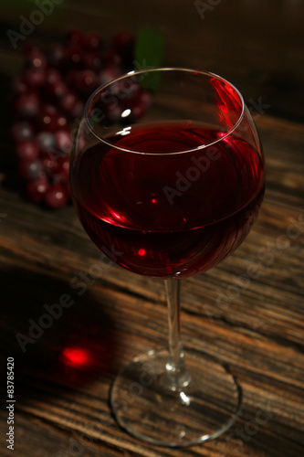 Red wine glass on brown wooden background