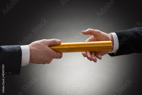 Fotografía  Two Hands Passing A Golden Relay Baton