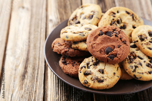 Tuinposter Koekjes Chocolate chip cookies on plate on brown wooden background