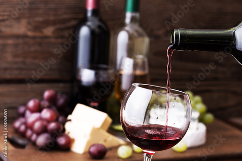 фотографія  Red wine pouring into glass, close-up.