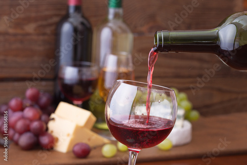 Photo  Red wine pouring into glass, close-up.