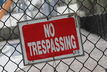 Red No Trespassing Sign On Fence