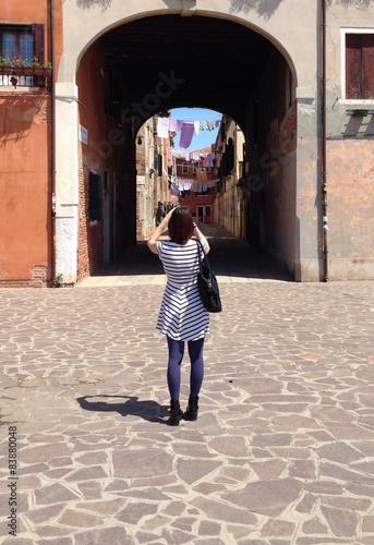 Photo  ragazza fa foto a bel paesaggo urbano con panni stesi