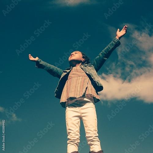 Fotografie, Obraz  Niña con brazos abiertos al cielo