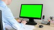 man works on desktop computer in the office - green screen