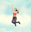 sporty teenage girl jumping in sportswear