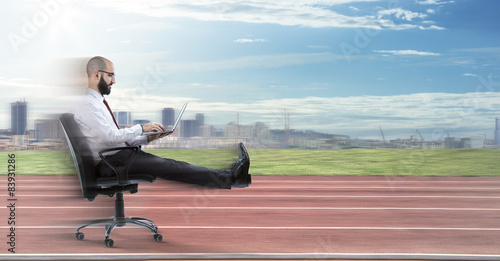 Fotografiet  Fast business - businessman sitting with laptop runs on track