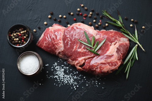 Fotografia  Raw ribeye steak with seasonings over black wooden surface