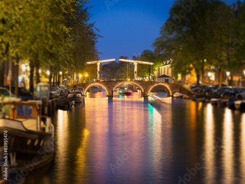 Photo  Tilt shift image of skinny bridge on canal in Amsterdam