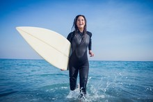 Woman In Wetsuit With A Surfbo...