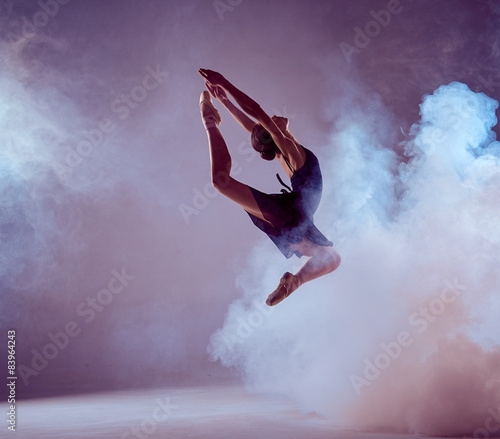 Fototapeta  Beautiful young ballet dancer jumping on a lilac background.