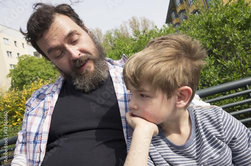 Photo  Vater und Sohn auf Parkbank in Wohnsiedlung. Berlin.