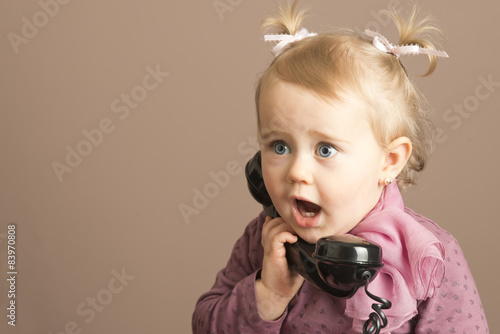 Fotografija  Baby girl in surprise talking on a vintage phone