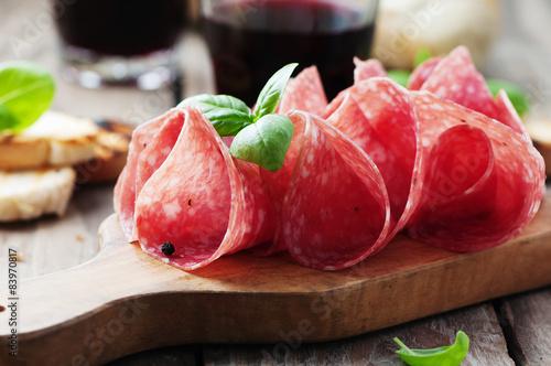 Fototapeta Delicious salami with basil and wine obraz
