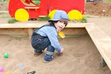 Cute Little Boy Plays In Sandpit