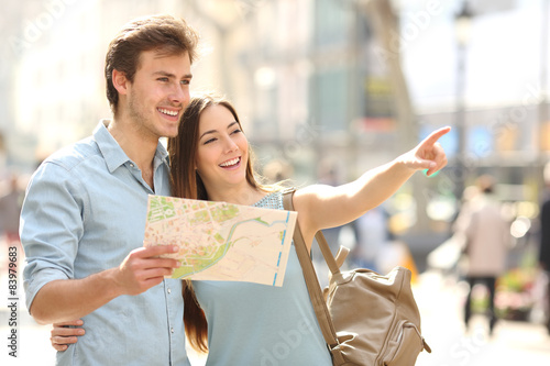 Foto  Couple of tourists consulting a city guide searching locations