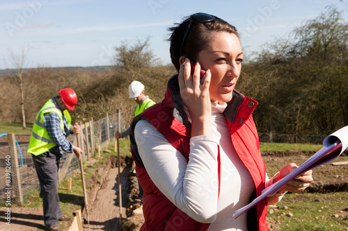 Canvas Prints Salmon Female construction organiser on the phone with male workers in