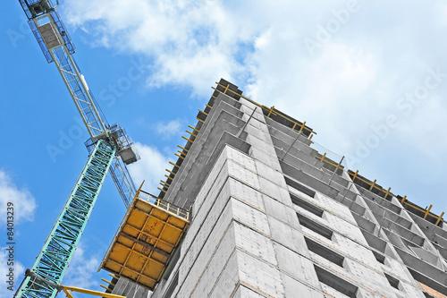 Láminas  Crane and building construction site against blue sky