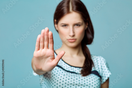 Lady making stop gesture with her palm, on a blue background